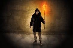 Caminante con la antorcha ardiente delante del concepto desmenuzable de la pared foto de archivo