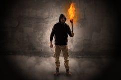 Caminante con la antorcha ardiente delante del concepto desmenuzable de la pared fotos de archivo