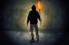 Caminante con la antorcha ardiente delante del concepto desmenuzable de la pared foto de archivo libre de regalías