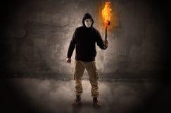 Caminante con la antorcha ardiente delante del concepto desmenuzable de la pared imagen de archivo