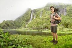 Caminante con la mochila delante de una cascada tropical Imágenes de archivo libres de regalías