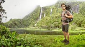Caminante con la mochila delante de una cascada tropical Foto de archivo