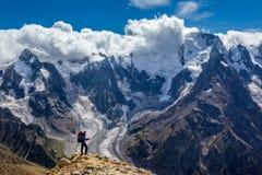 Caminante con la mochila que se coloca en la montaña superior y que disfruta de escena Imagenes de archivo