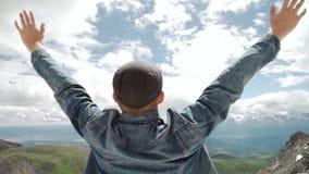 Caminante con la mochila que se coloca encima de una montaña con las manos aumentadas y que disfruta de salida del sol almacen de metraje de vídeo