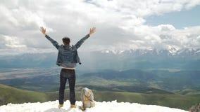Caminante con la mochila que se coloca encima de una montaña con las manos aumentadas y que disfruta de salida del sol almacen de video