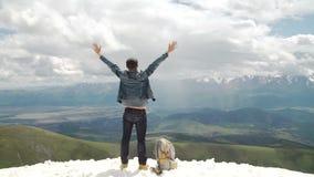Caminante con la mochila que se coloca encima de una montaña con las manos aumentadas y que disfruta de salida del sol metrajes