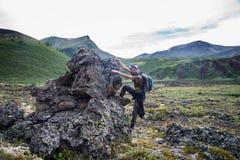 Caminante con la mochila que sube hasta piedra congelada de la lava en valey del voolcano Mountain View hermoso Fotos de archivo libres de regalías