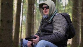 Caminante con la tableta que se sienta en bosque almacen de metraje de vídeo