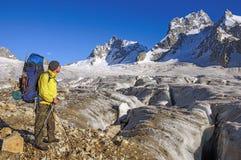Caminante con una mochila en un glaciar Imágenes de archivo libres de regalías