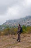 Caminante de la colina que se coloca en el medio de desierto de montaña Imagenes de archivo