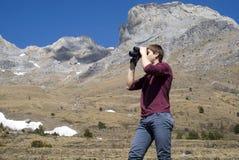 Caminante de la montaña que mira a través de los prismáticos Fotos de archivo libres de regalías