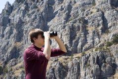 Caminante de la montaña que mira a través de los prismáticos Fotos de archivo