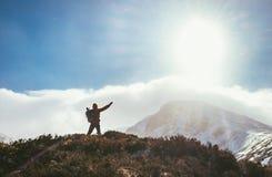 Caminante de la montaña que saluda el sol en montañas foto de archivo