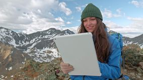 Caminante de la muchacha con una tableta que se sienta en una roca en un fondo de las montañas y de los lagos, Noruega almacen de video
