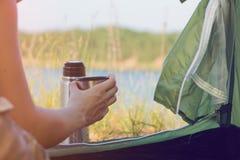 Caminante de la muchacha en una tienda y sostener una taza de té caliente Montañas y lago en el fondo Imagen de archivo