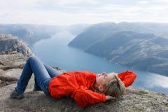 Caminante de la mujer en la roca/Preikestolen, Noruega del púlpito Fotos de archivo