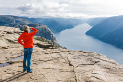 Caminante de la mujer en la roca/Preikestolen, Noruega del púlpito Fotografía de archivo libre de regalías