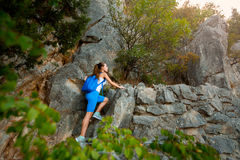 Caminante de la mujer joven con la mochila que camina un rastro en montañas rocosas Imagen de archivo