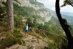 Caminante de la mujer joven con la mochila que camina un rastro en montañas rocosas con un palillo en su mano Fotografía de archivo