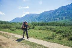 Caminante de la mujer joven con los polos de la mochila y del senderismo en un día soleado en rastro de montaña Imagenes de archivo
