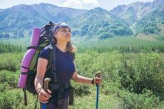 Caminante de la mujer joven con los polos de la mochila y del senderismo en un día soleado en rastro de montaña Foto de archivo