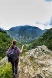 Caminante de la mujer joven que admira la montaña hermosa Fotografía de archivo