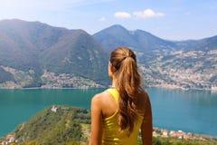 Caminante de la mujer joven que se coloca de admiración de una opinión de la cima de la montaña que mira hacia fuera sobre gamas  imágenes de archivo libres de regalías