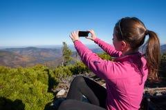 Caminante de la mujer joven que toma la foto con el teléfono celular foto de archivo
