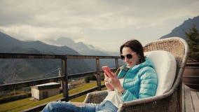 Caminante de la mujer joven que toma la foto con el teléfono elegante en el pico de montaña almacen de video