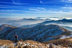 Caminante de la mujer joven que toma la foto con la cámara en pico de montañas imagen de archivo libre de regalías
