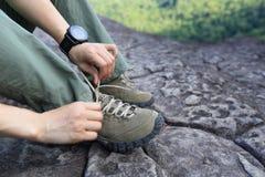 Caminante de la mujer que ata el cordón en pico de montaña Imagen de archivo libre de regalías