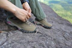 Caminante de la mujer que ata el cordón en roca del pico de montaña Fotos de archivo
