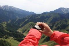 Caminante de la mujer que comprueba el altímetro en el reloj de los deportes en el pico de montaña imágenes de archivo libres de regalías
