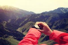Caminante de la mujer que comprueba el altímetro en el reloj de los deportes en el pico de montaña fotos de archivo libres de regalías