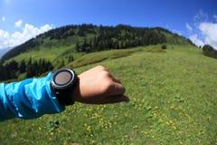 Caminante de la mujer que comprueba el altímetro en el reloj de los deportes en el pico de montaña fotografía de archivo