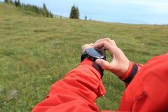 Caminante de la mujer que comprueba el altímetro en el reloj de los deportes en el pico de montaña foto de archivo
