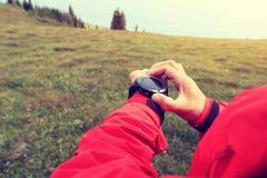 Caminante de la mujer que comprueba el altímetro en el reloj de los deportes en el pico de montaña imagenes de archivo