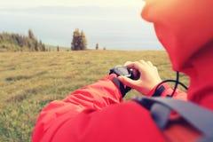 Caminante de la mujer que comprueba el altímetro en el reloj de los deportes en el pico de montaña fotos de archivo