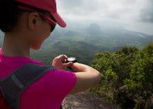 Caminante de la mujer que comprueba el altímetro en pico de montaña de la playa foto de archivo libre de regalías