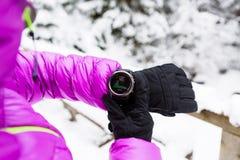 Caminante de la mujer que comprueba el reloj de los deportes en bosque y montañas del invierno imagenes de archivo