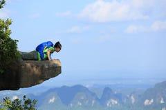 Caminante de la mujer que mira abajo en el acantilado del pico de montaña Imágenes de archivo libres de regalías