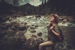 Caminante de la mujer que se coloca cerca del río salvaje de la montaña Foto de archivo