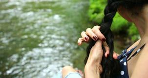 Caminante de la mujer que se sienta cerca y que tuerce la cascada de la trenza en bosque profundo almacen de metraje de vídeo