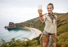 Caminante de la mujer que toma el selfie con smartphone delante del océano Imágenes de archivo libres de regalías