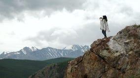 Caminante de la mujer que toma la foto con el teléfono elegante en el acantilado del pico de montaña almacen de video