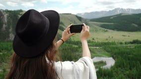 Caminante de la mujer que toma la foto con el teléfono elegante en el acantilado del pico de montaña metrajes