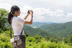 Caminante de la mujer que toma la foto con la cámara en la montaña foto de archivo libre de regalías