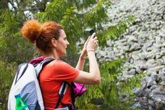 Caminante de la mujer que toma las fotos con el teléfono móvil fotografía de archivo libre de regalías