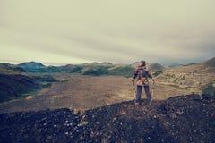 Caminante de la señora con la mochila que se coloca encima de la montaña, visión desde el pico del volcán al valle congelado de l Imagen de archivo
