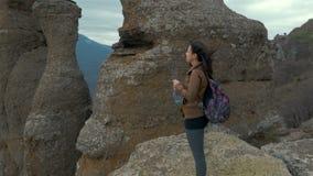 Caminante de la señora joven con la mochila, con el top de la montaña almacen de metraje de vídeo